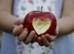 Child holding heart apple